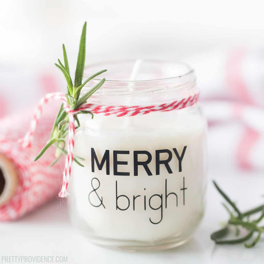 White scented soy wax candle in a small baby food jar decorated with vinyl label 'Merry & Bright' and Christmas trim