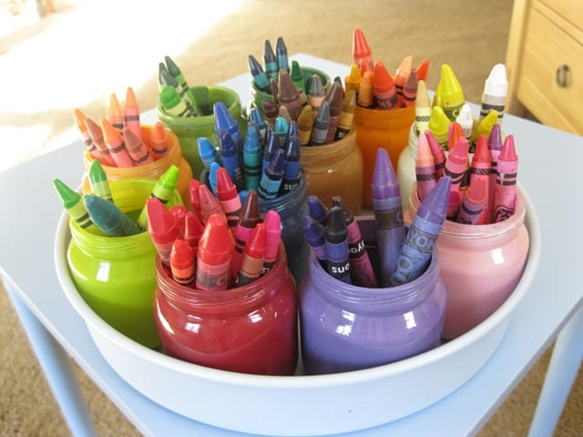 Baby food jars painted colors and crayons sorted into them in a white lazy susan - organized crayons!