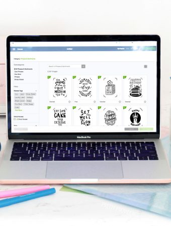 Cricut access on the screen of a Macbook Pro and Cricut supplies around it.
