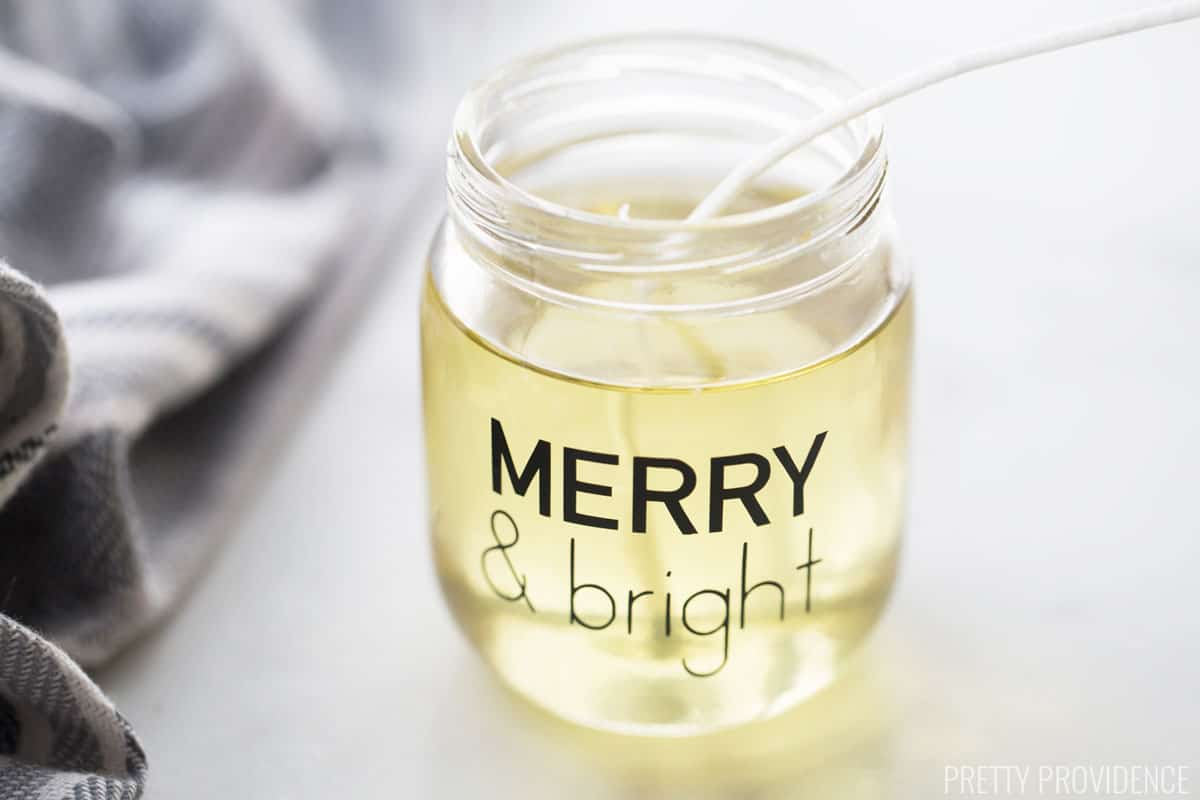 Melted soy wax candle inside a small jar with a label 'Merry & bright'