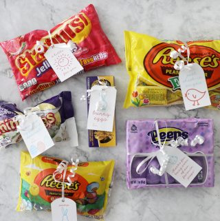 six bags of easter candy with easter gift tags tied on with white ribbon