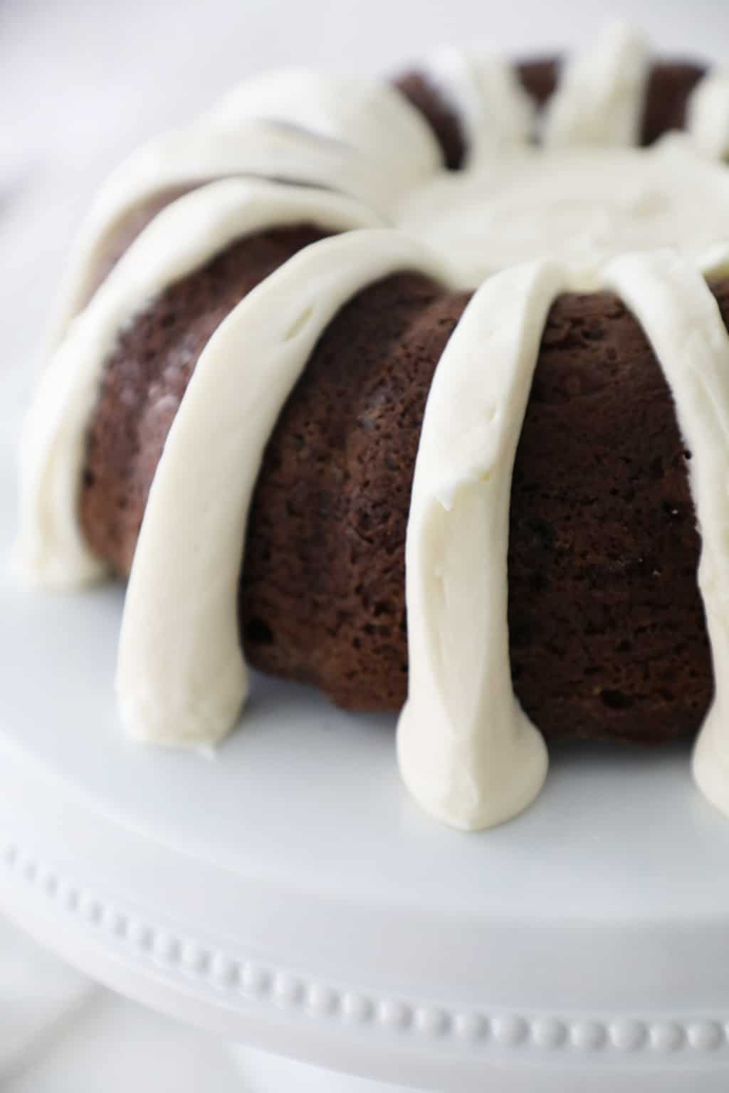 chocolate bundt cake with cream cheese frosting on a white cake stand