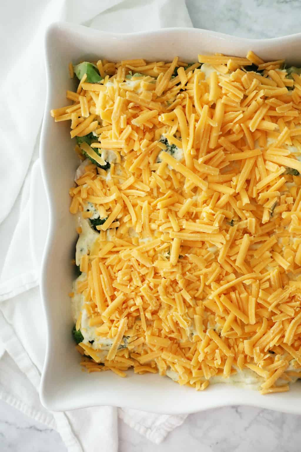 a casserole dish filled with casserole with unmelted cheese on the top