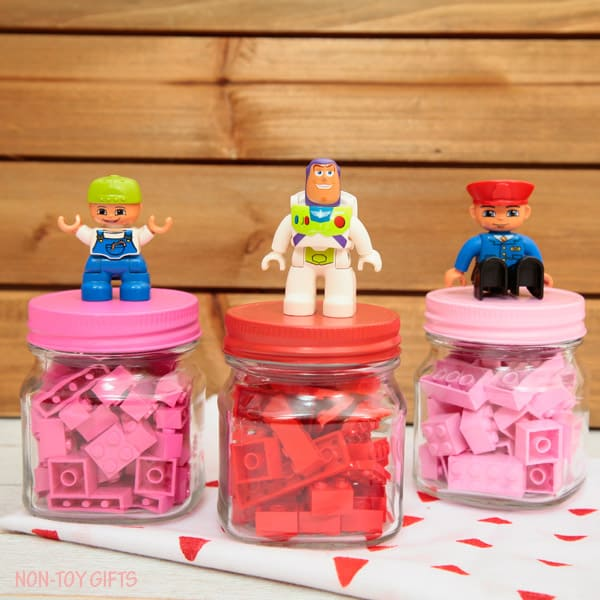Pink legos and red legos in jars with minifigures glued to the lids - cute toy Valentine idea