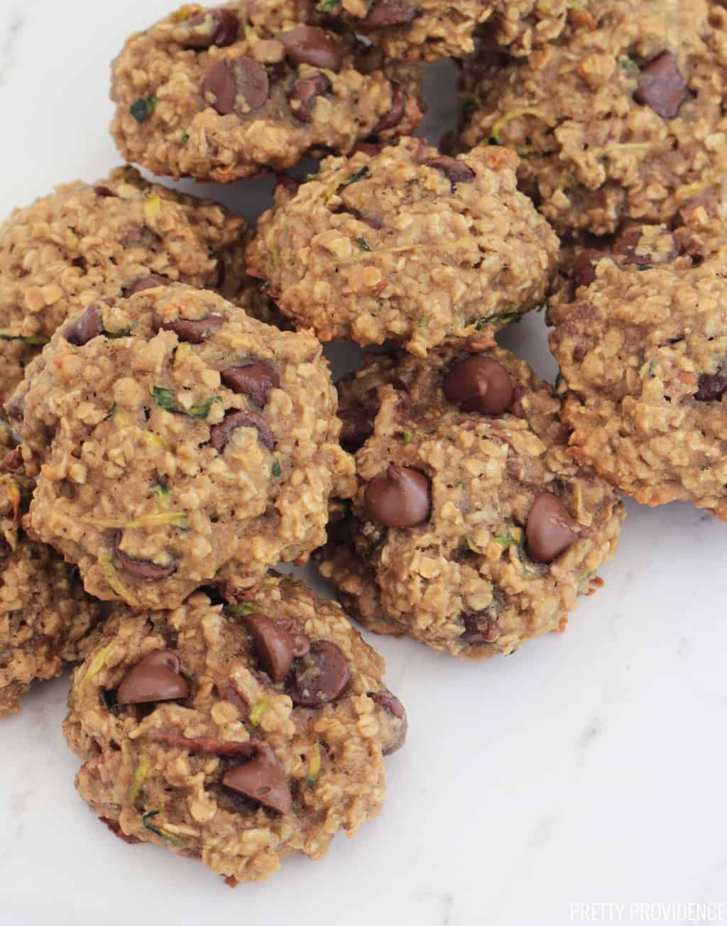 Zucchini breakfast cookies with oatmeal and chocolate chips on a white marble surface.