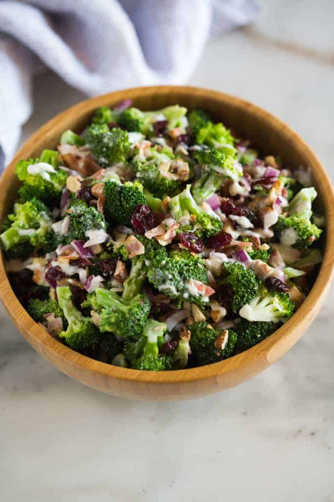 broccoli salad in a wooden bowl on a granite counter with a blue tea towel in background