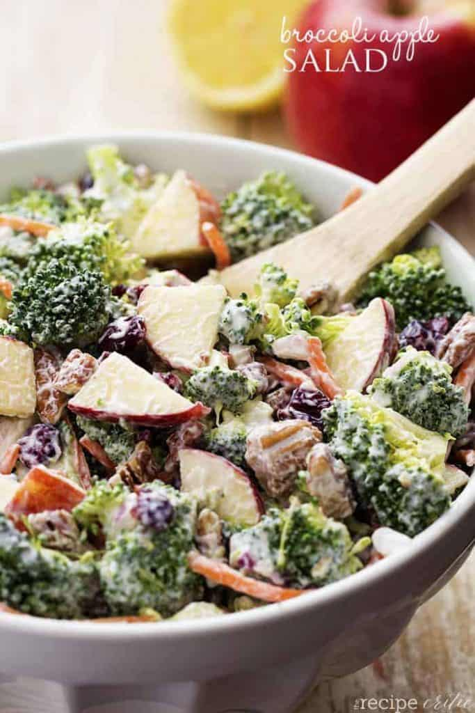 a grey salad bowl filled with broccoli salad with an apple in the background and a wooden spoon
