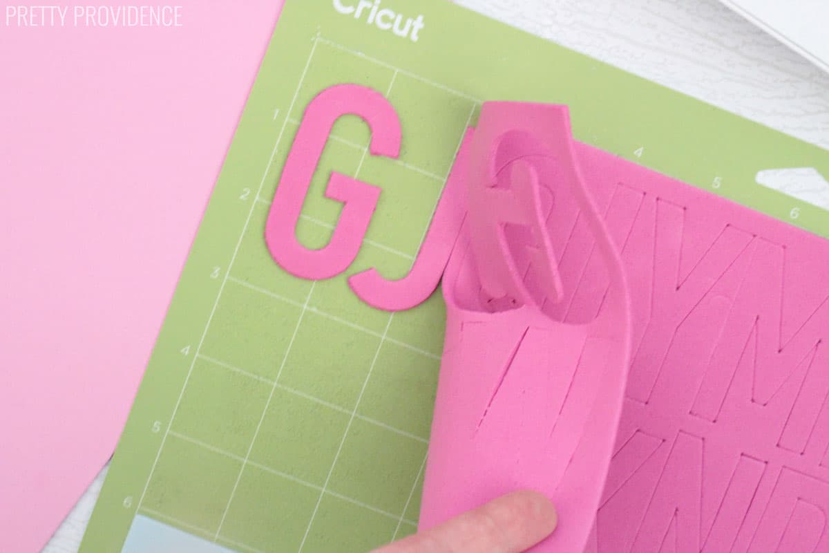 Craft foam bath letters G and J being pulled off a Cricut mat.