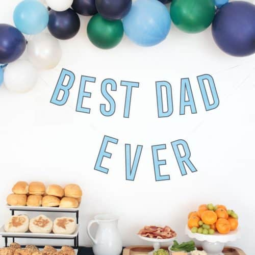 Father's Day breakfast table with breakfast sandwich ingredients, balloons and 'best dad ever' banner.