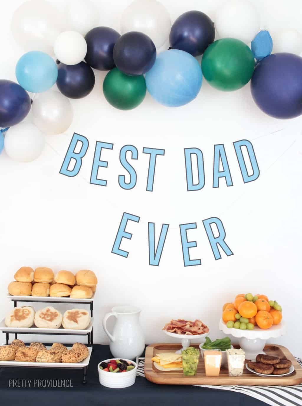 Father's Day breakfast table with breakfast sandwich ingredients, balloons and free printable 'best dad ever' banner.