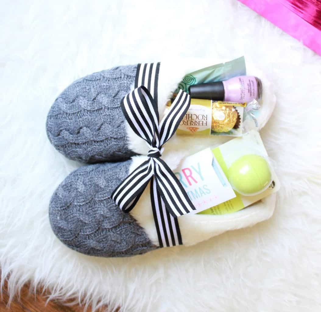 grey slippers filled with treats on a white faux fur rug