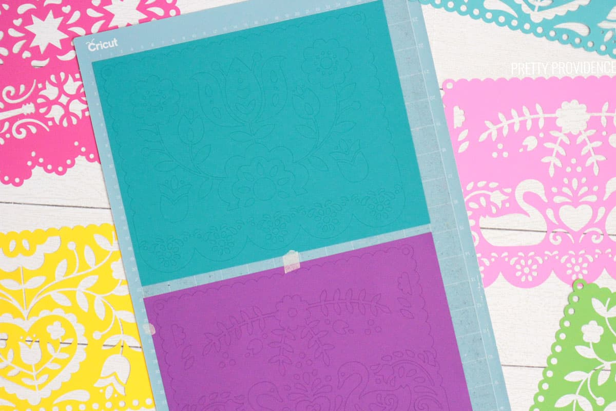 Teal and purple card stock on a blue Cricut LightGrip mat, papel picado pieces surrounding