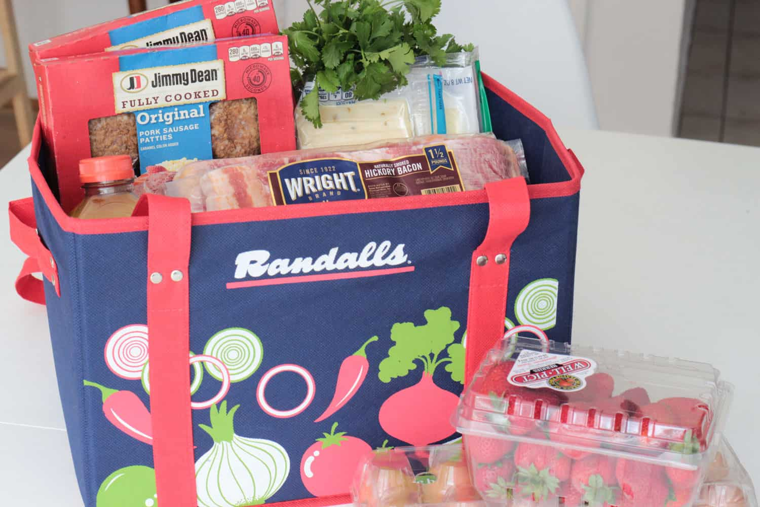 Randall's reusable grocery tote with Wright brand bacon, Jimmy Dean sausage, cheese and cilantro in it.