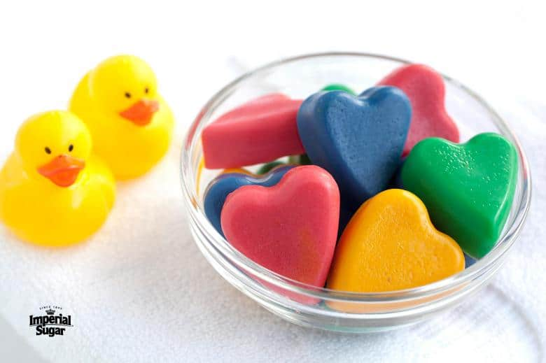 heart shaped bath crayons in a clear bowl with rubber duckies next to it.