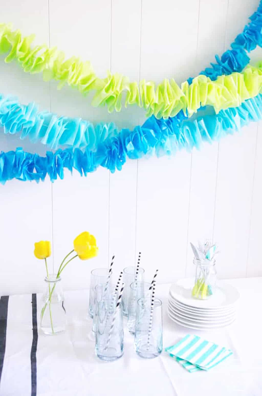ruffled garlands in blue and green hanging over a white dinner table and yellow flowers