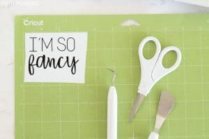 'I'm So Fancy' design on Cricut mat with weeding tools and scissors