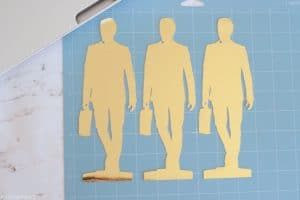 Gold foil card stock business man statues on blue Cricut lightgrip mat