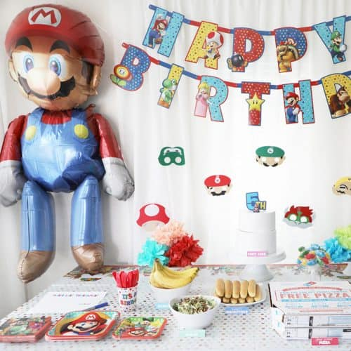 large mario balloon next to a happy birthday banner and party table