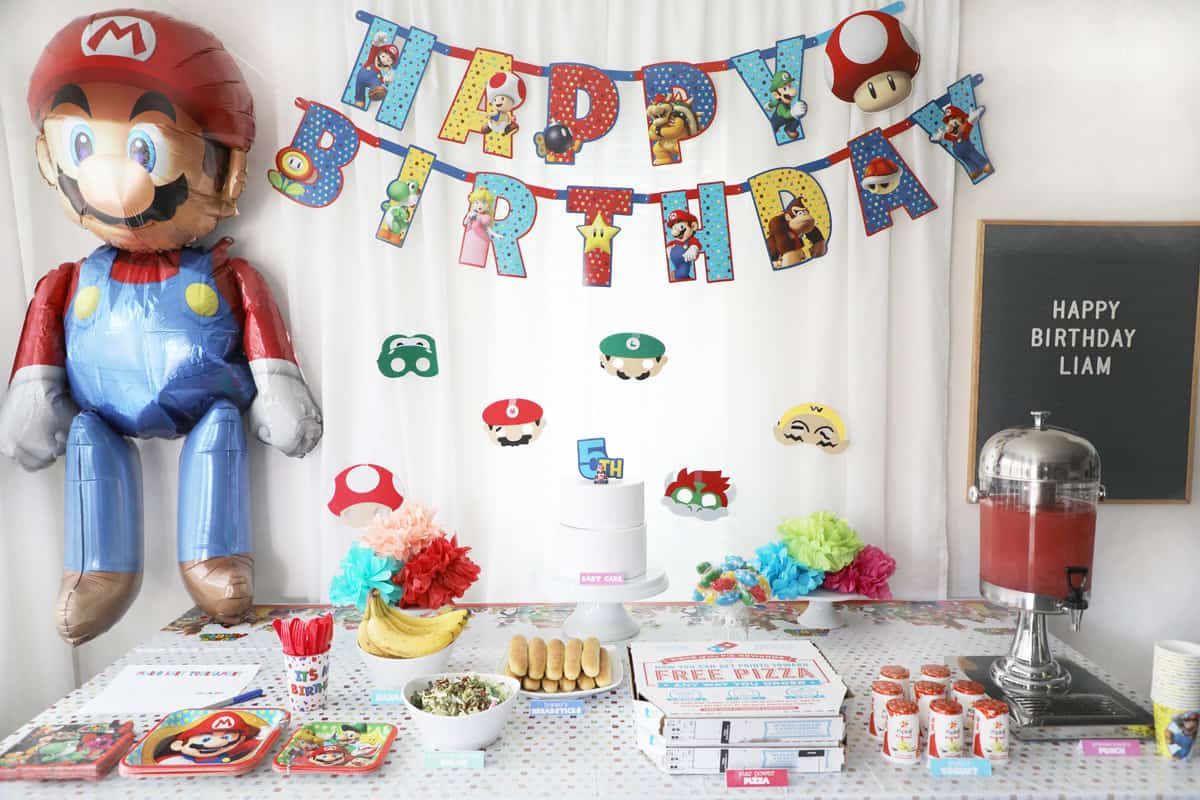 a Mario birthday party set up against a white curtain