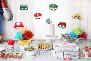 mario character masks hung on a white curtain in front of a party table