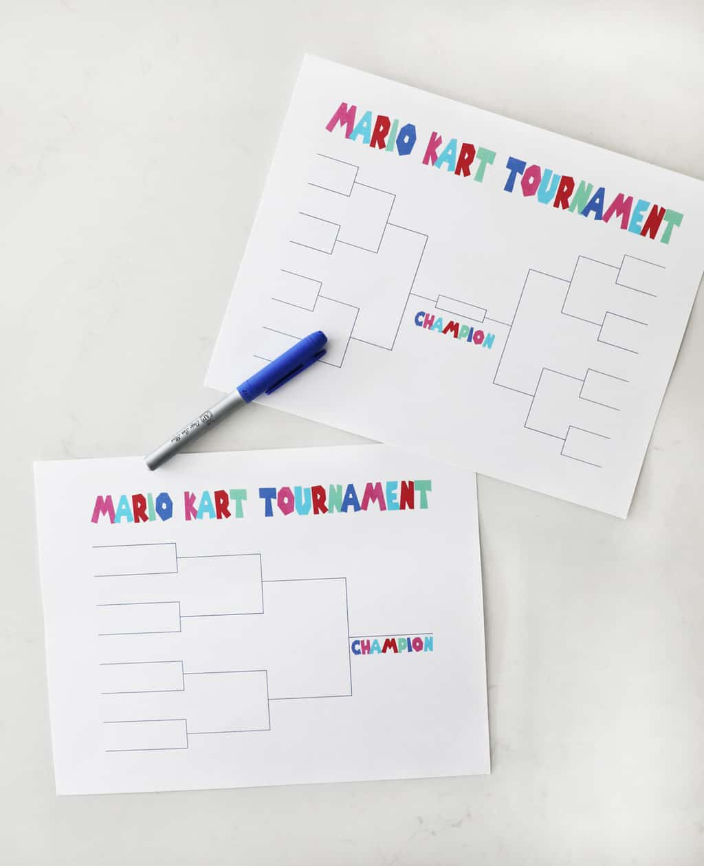 two printable mario kart tournament brackets on a white countertop with a blue sharpie