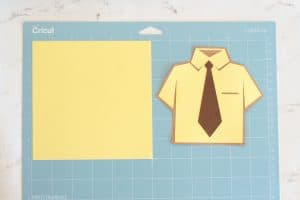 Dwight Schrute shirt final and a square yellow piece of card stock on a blue cricut mat.