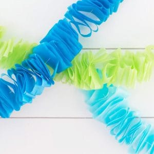 two blue and one green tissue paper garlands hung against a white wood backdrop