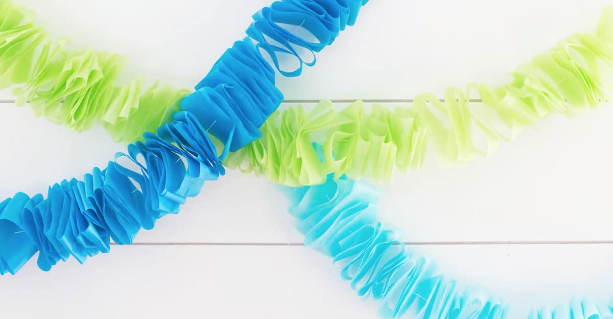 three ruffled garlands strung against a white wood wall. one lime green, two blue