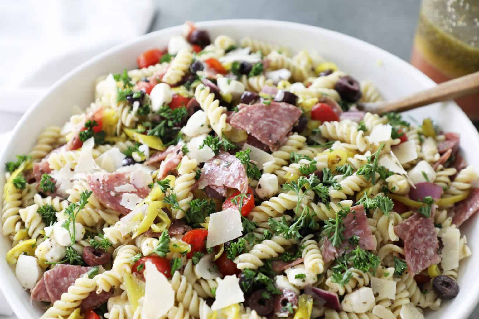 top half of a bowl of pasta salad with a white napkin on the left and salad dressing on the top right