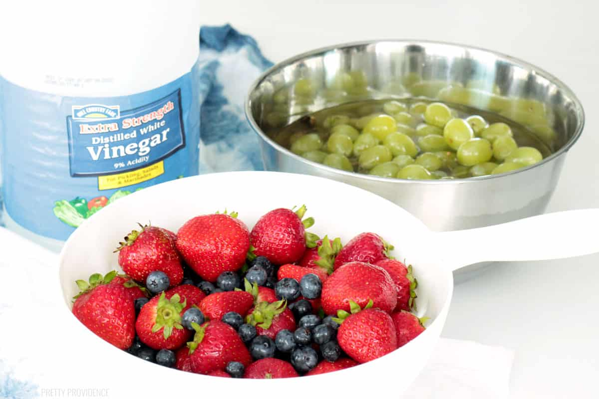 Vinegar fruit wash and strawberries, blueberries and grapes in bowls.