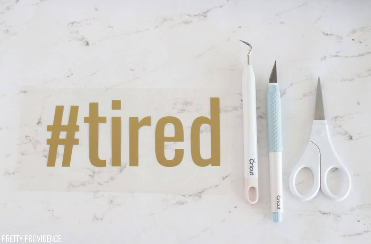 gold iron-on with word '#tired' and weeding tools, scissors next to it