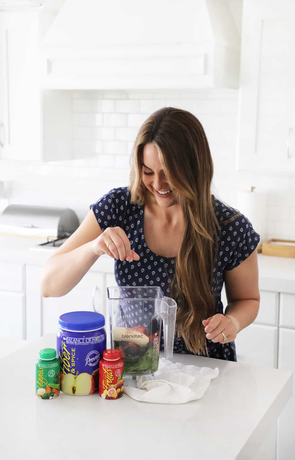 a woman emptying a fruit capsule into a smoothie in a white kitchen
