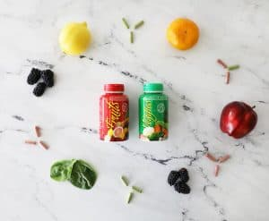 BON fruit and veggie capsules surrounded by fresh fruits and veggies