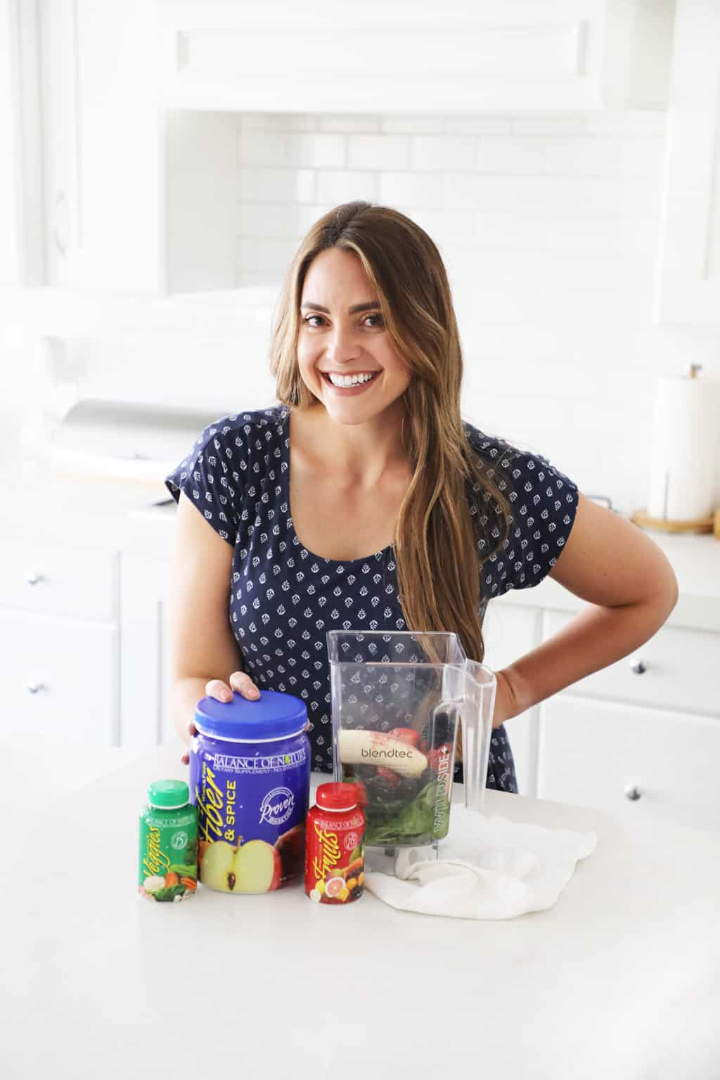 a woman standing in a white kitchen touching the balance of nature supplements next to a blender