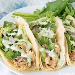 Crockpot shredded chicken tacos on a white plate topped with lettuce and cilantro.