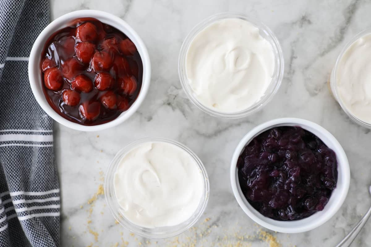 cream cheese pies next to small white bowls with cherry and blueberry pie filling