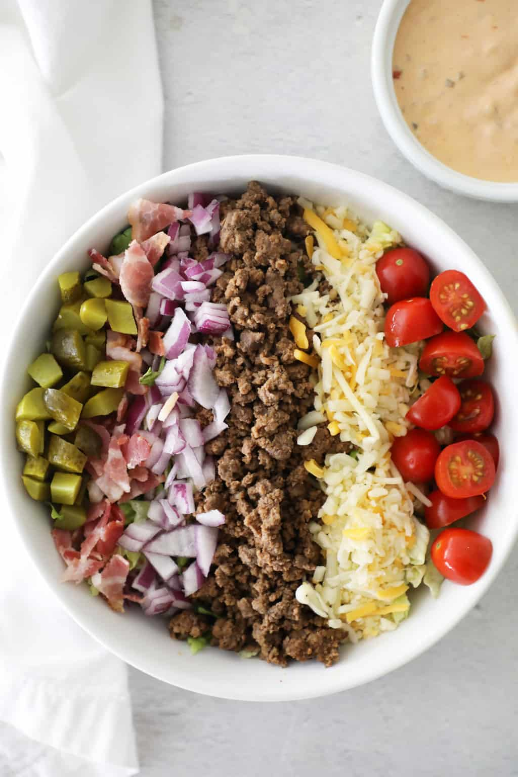 all the ingredients of a cheeseburger chopped small and covering lettuce in a white bowl