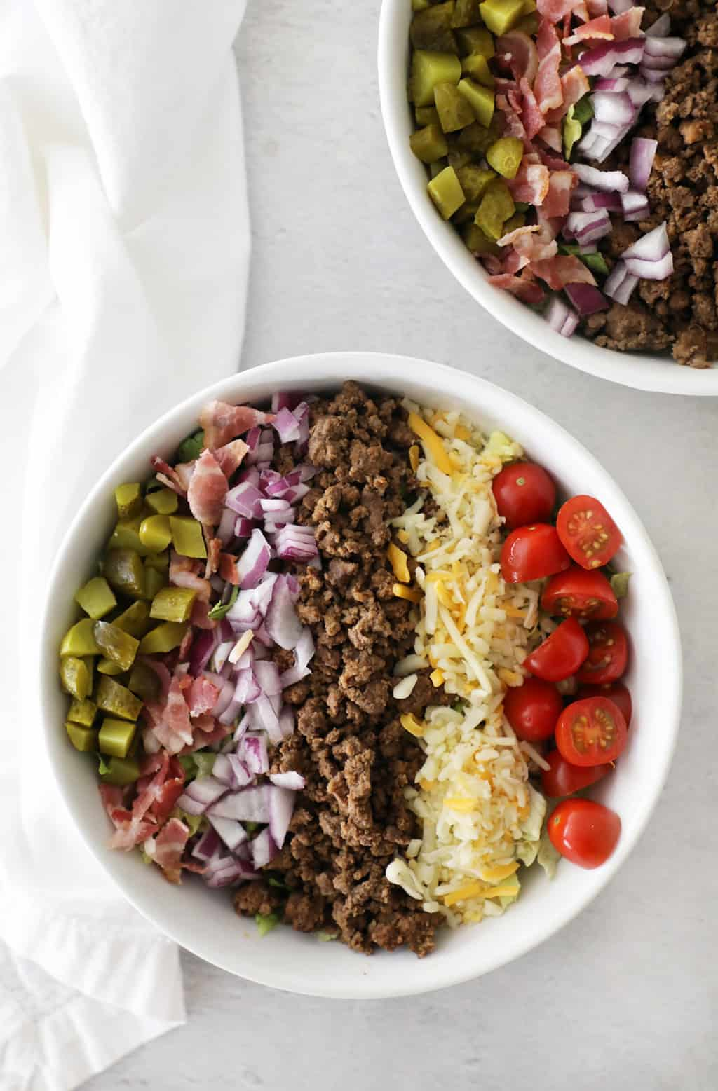 two bowls of burger salad with the ingredients lined in strips across the top