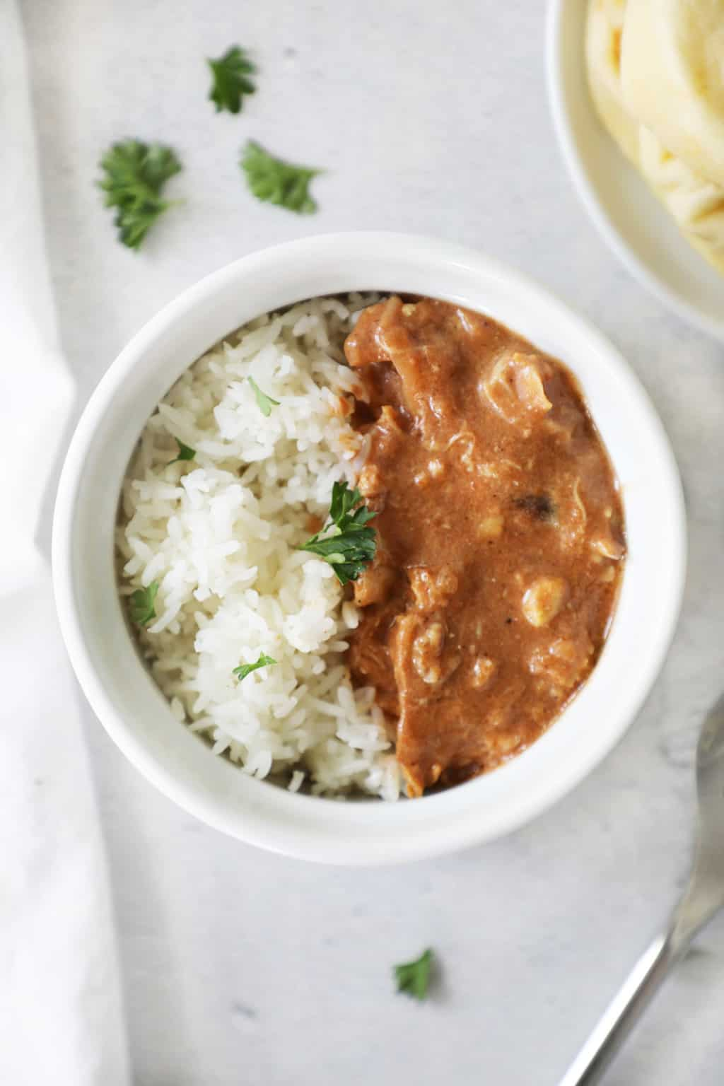 rice and tikka masala in a bowl on a cement counter