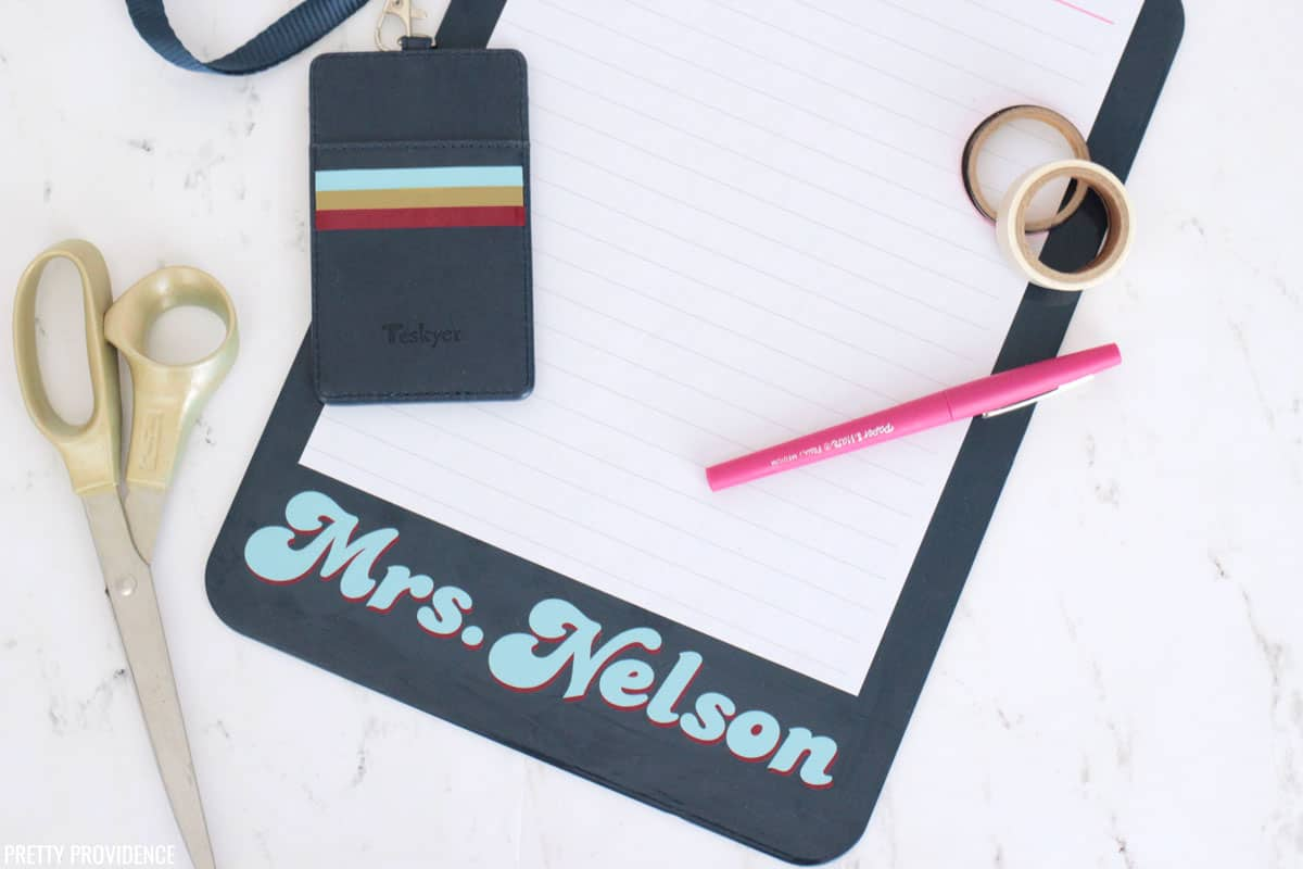 Navy blue clipboard with 'Mrs. Nelson' in vinyl and striped badge holder