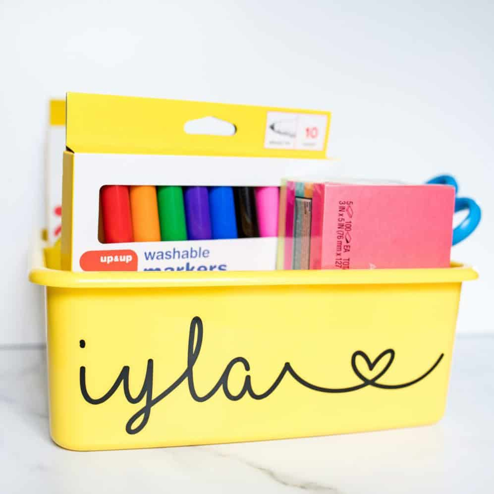 "Yellow bin personalized with cursive name ""iyla"" in black vinyl"