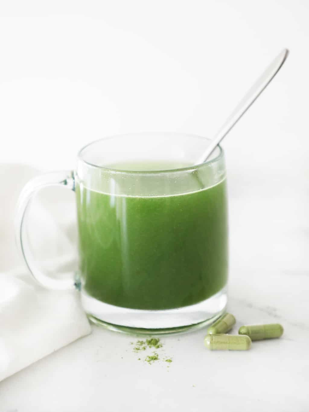 BON veggie capsules diluted in water in a clear mug with a spoon sticking out
