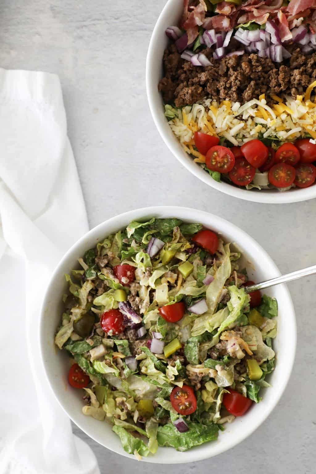 two hamburger salads in white bowls on a white marble countertop with a white tea towel