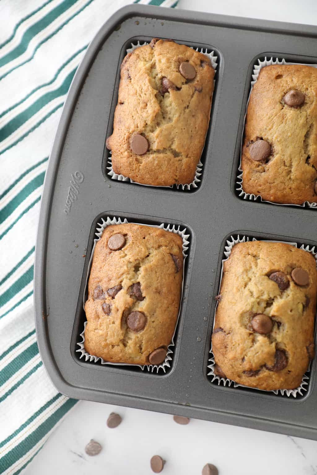 chocolate chip banana bread loaves baked in the pan next to a tea towel