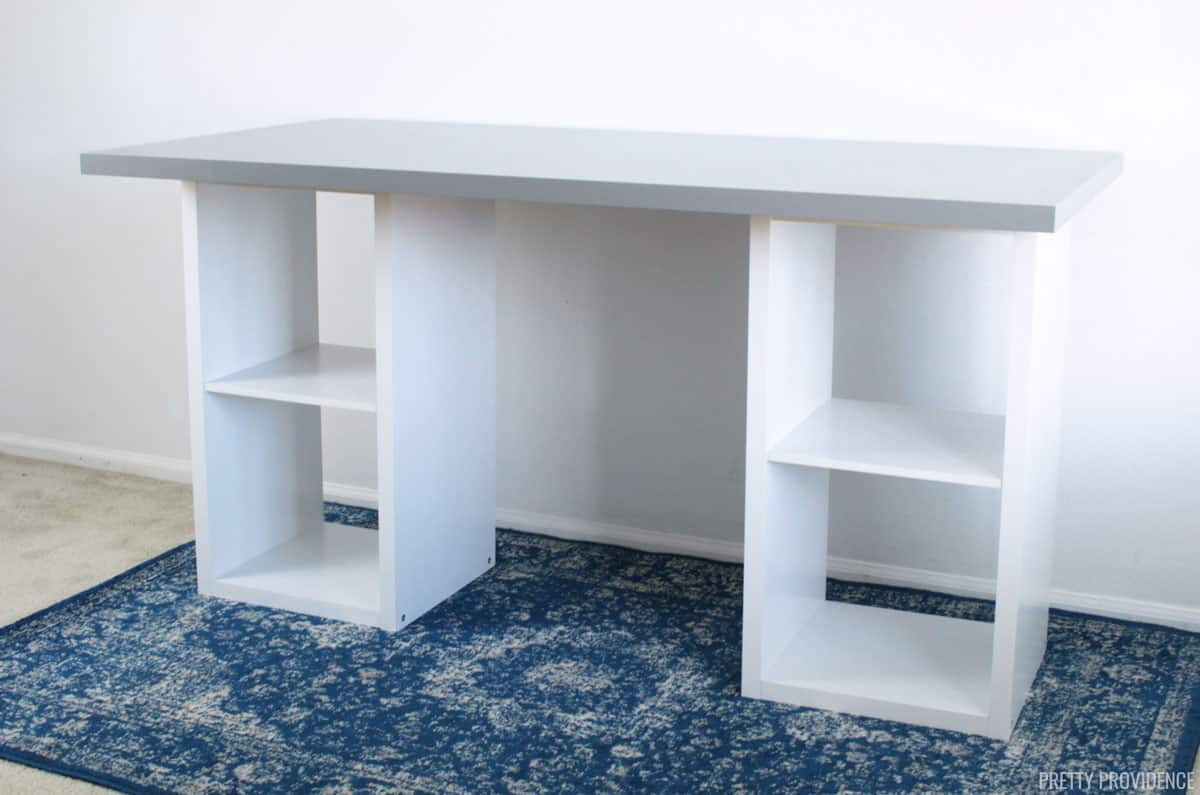 white cube bookshelves with gray Linnmon IKEA desk top on a blue rug