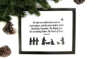 nativity scene in a thin black frame on a white background by a garland