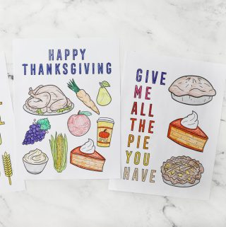 two colored thanksgiving coloring pages on a white counter