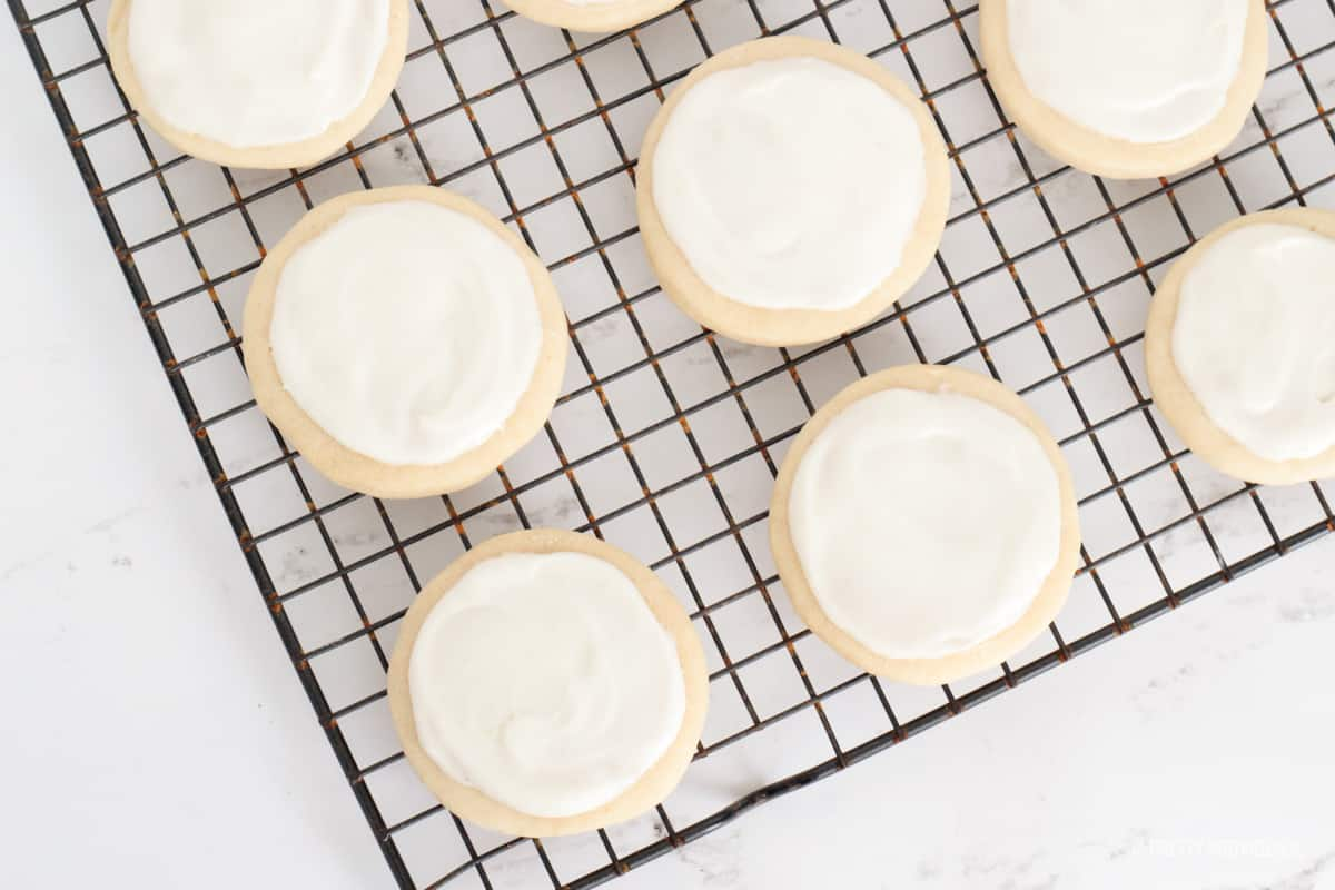 White frosting on top of round cookies on a cooling rack