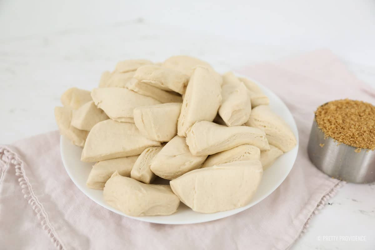 Biscuits cut in half on a white plate with brown sugar to the side