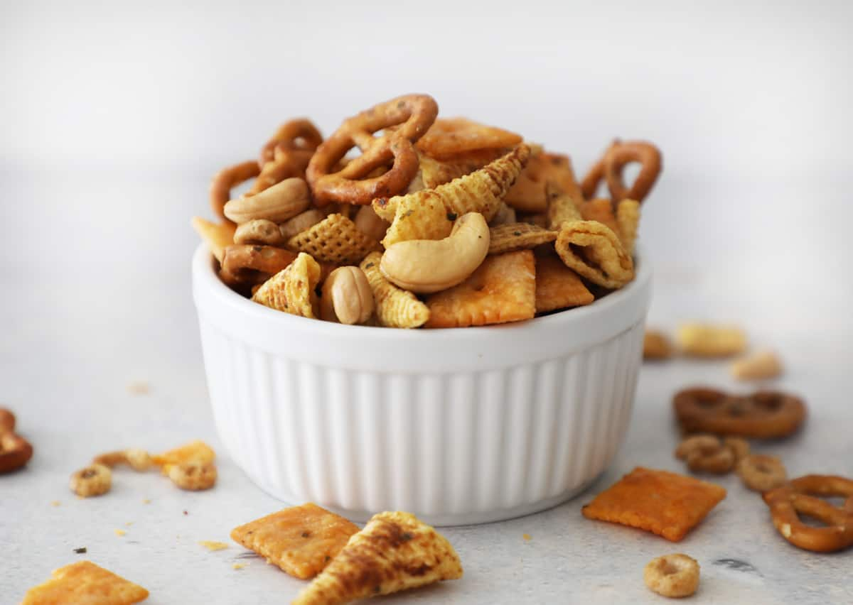 a white bowl on a white counter overflowing with homemade Chex mix